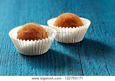 Vegan homemade yummy cocoa truffles in paper cups on navy blue background closeup