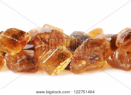 Line made of brown rock sugar crystals isolated over the white background