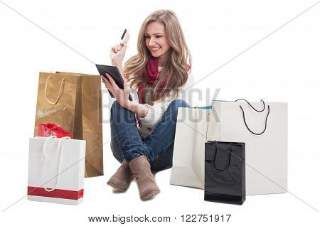 Beautiful and happy shopping woman holding credit or debit card and tablet with shopping bags arround her