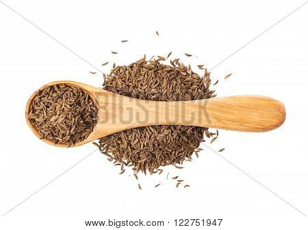 Wooden spoon over the pile of cumin seeds isolated over the white background