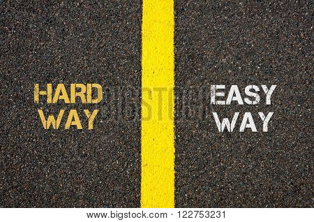 Antonym concept of HARD WAY versus EASY WAY written over tarmac, road marking yellow paint separating line between words