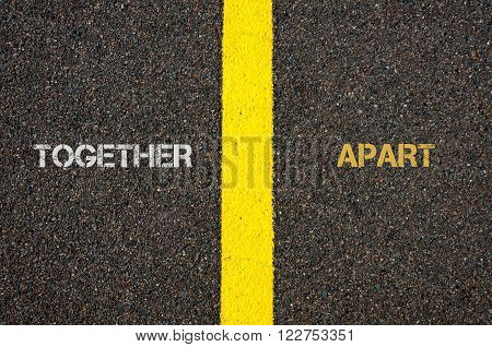 Antonym concept of TOGETHER versus APART written over tarmac, road marking yellow paint separating line between words