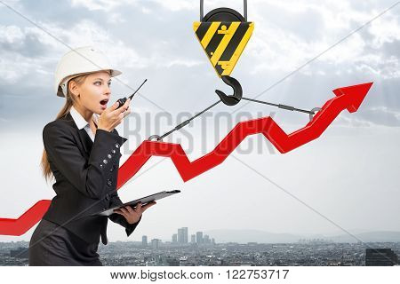 Businesslady with walkie-talkie set and graphical chart