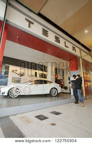 BRUSSELS, BELGIUM, WEDNESDAY, MARCH 9, 2016: Pedestrians walk past a showroom of Tesla Motors, Inc. Tesla produces high-end electric cars.