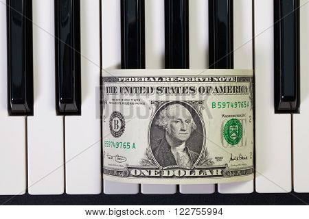 Detail of piano keyboard and US dollar banknote