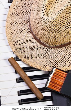 Detail of piano keyboard,straw hat and luxury cigar