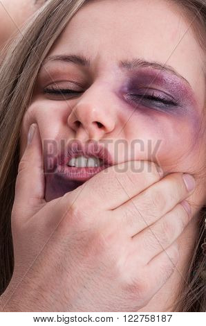 Scared woman getting beaten by aggressive man. Domestic violence concept with injuries and bruises