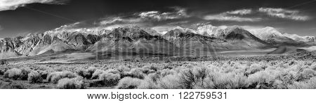 Black & White Panorama of the southern tip of the Sierra Nevada Mountains located in Central California under a clear blue sky with wispy white clouds.