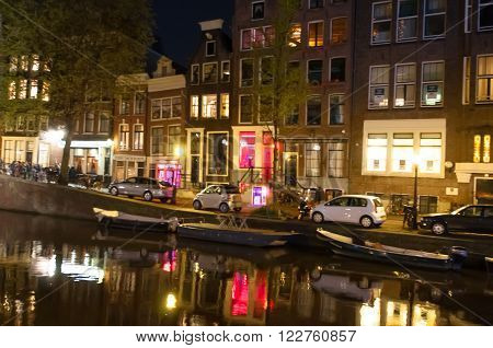 AMSTERDAM-APRIL 29: Red light district at night on April 29 2015. The red-light district is a part of city there is a concentration of prostitution and sex-oriented businesses.