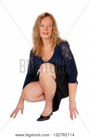 A beautiful blond woman crouching on the floor in a black skirt and navy