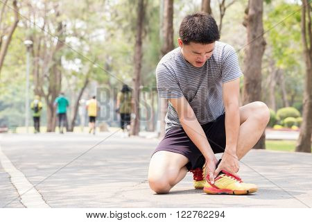 Sports injury. Man with pain in ankle while jogging in park