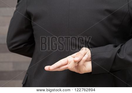 Dishonesty Business fraud concept Businessman showing fingers crossed