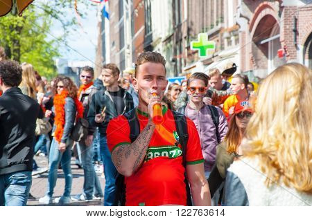 AMSTERDAM-APRIL 27: Undefined person play the pipe crowd of People have fun on Amsterdam street During King's Day on April 272015. King's Day is the largest open-air festivity in Amsterdam.
