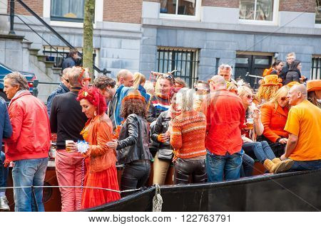 AMSTERDAM-APRIL 27: Locals and tourists celebrate King's Day also known as Koningsdag on April 272015 the Netherlands. King's Day is the largest open-air festivity in Amsterdam.
