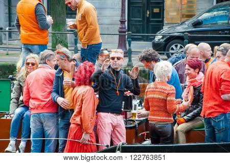 AMSTERDAMNETHERLANDS-APRIL 27: Cheerful people in orange dance and have fun on a boat during King's Day on April 272015. King's Day is the largest open-air festivity in Amsterdam.