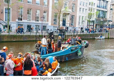 AMSTERDAMNETHERLANDS-APRIL 27: Cheerful people in orange have fun on a boat during King's Day on April 272015. King's Day is the largest open-air festivity in Amsterdam.