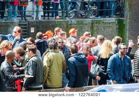 AMSTERDAM-APRIL 27: King's Day boating locals have fun on the boats on April 27 2015 in Amsterdam the Netherlands.