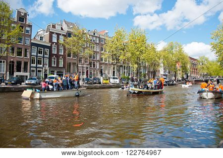AMSTERDAMNETHERLANDS-APRIL 27: Amsterdam canal full of boats during King's Day on April 27 2015 the Netherlands. Kings Day is biggest festival celebrating the birth of Dutch royalty.