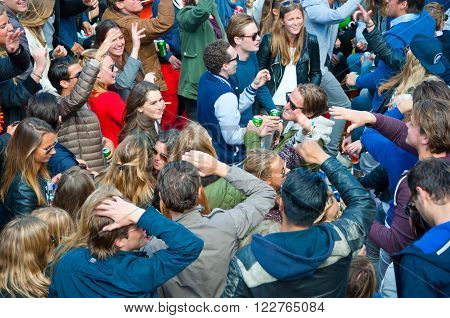 AMSTERDAM - APRIL 27: Open-air party people dance during King's Day on April 27, 2015 in Amsterdam the Netherlands. Kings Day is the biggest festival celebrating the birth of Dutch royalty.