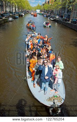 AMSTERDAM, NETHERLANDS - APRIL 27: People on Party Boat with unlimited beer soda and wine aboard on King's Day on April 27, 2015. King's Day is the largest open-air festivity in Amsterdam.