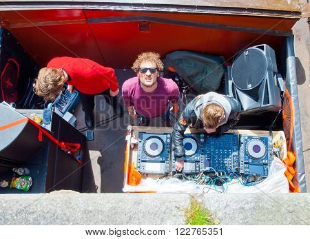 AMSTERDAM, NETHERLANDS - APRIL 27: DJ on boat party on Amsterdam canal during King's Day on April 27, 2015 in Amsterdam. Kings Day is biggest festival celebrating the birth of Dutch royalty.