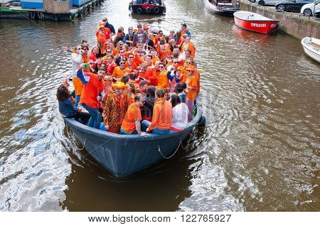 AMSTERDAMNETHERLANDS-APRIL 27: Crowd of local people dressed in orange celebrate King's Day in a boat on April 272015 in Amsterdam. King's Day is the largest open-air festivity in Amsterdam.