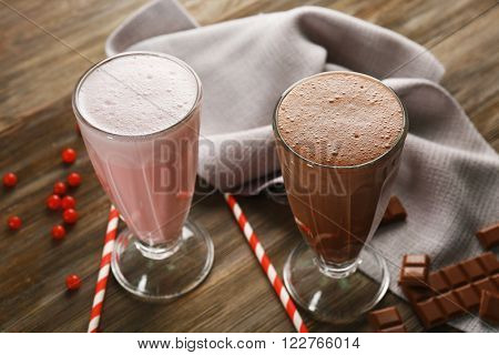Glasses of chocolate and fruit milkshakes on wooden table closeup