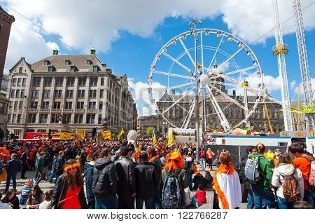 AMSTERDAMNETHERLANDS-APRIL 27: Dam Square full of people dressed in orange during King's Day on April 272015 in Amsterdam. King's Day is the largest open-air festivity in Amsterdam.