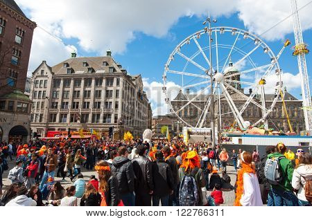 AMSTERDAMNETHERLANDS-APRIL 27: Dam Square full of locals and tourists dressed in orange on King's Day on April 272015 in Amsterdam. King's Day is the largest open-air festivity in Amsterdam.