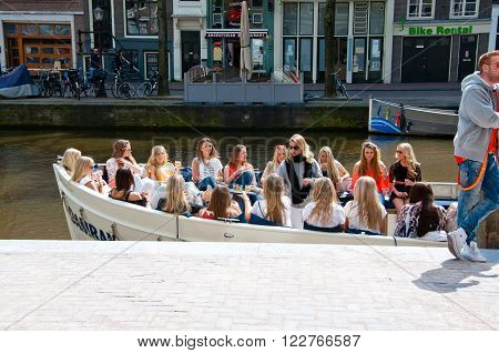 AMSTERDAMNETHERLANDS-APRIL 27: Group of girls in a boat celebrate King's Day on April 272015 in Amsterdam the Netherlands. King's Day is the largest open-air festivity in Amsterdam.