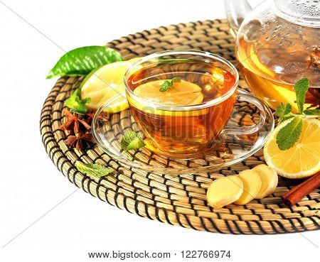 Cup of tea with ginger on a wicker mat isolated on white