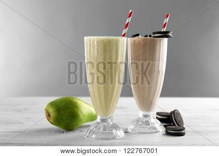 Glass of milk cocktail with pear and chocolate cookies on grey background