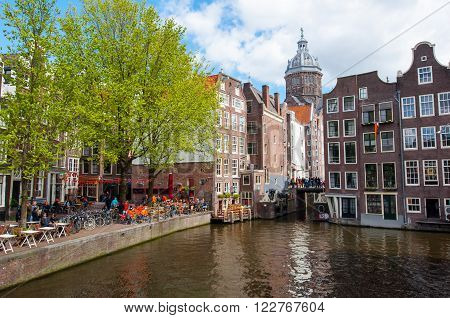Amsterdam-April 27: Red light district crowd of tourists celebrate King's Day in a local cafe the Church of St. Nicholas is visible in the distance on April 272015 the Netherlands.