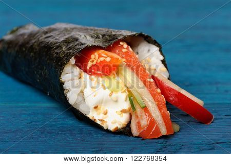 Japan temaki sushi in nori with rice salmon cream cheese bell pepper and sesame seeds on navy blue background closeup