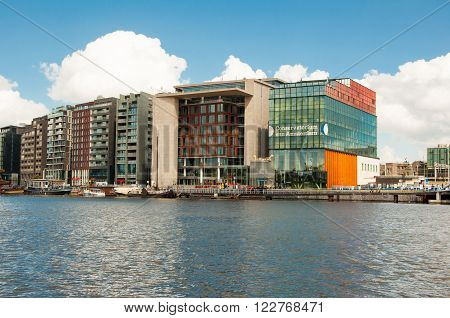 AMSTERDAM-APRIL 27: Oosterdokseiland with the Amsterdam Central Library in the middle and Amsterdam Conservatory in the right on April 272015 in Amsterdam the Netherlands.