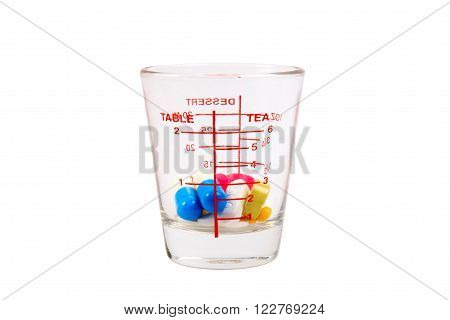 Many Colorful Pills In A Measuring Cup Of Glass On White Background.