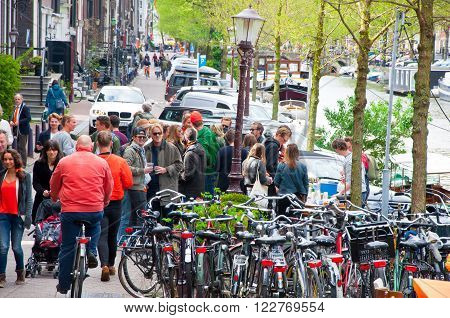 AMSTERDAMNETHERLANDS-APRIL 27: Crowd of locals celebrate King's Day on April 272015 in Amsterdam the Netherlands. The King Day is celebrated every year in April 27.