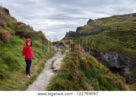 Child Standing On A Tintagel Bay North Cornwall Coast, England