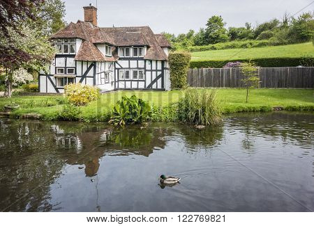 LOOSE, KENT, UK, 11 MAY 2015 - Pretty half timbered cottage in the village of Loose, Kent, UK with the Loose river in the foreground