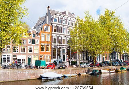 AMSTERDAMNETHERLANDS-APRIL 27: Amsterdam canal with cars and boats along the bank on April 27 2015 in Amsterdam the Netherlands.
