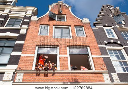 AMSTERDAMNETHERLANDS APRIL 27: Local youth celebrate King's Day in city center on April 27 2015 in Amsterdam Netherlands. King's Day is the biggest street party of the year.