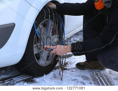 Mechanic Mounting Snow Chains In The Car Tyre In Winter On Snow