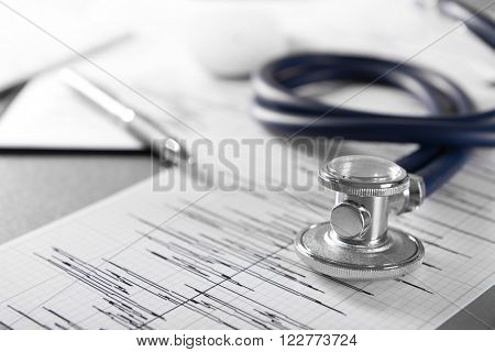 Cardiogram chart with medical stethoscope on table closeup