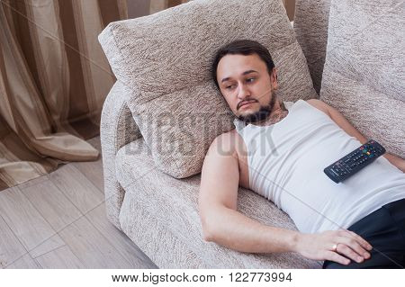 a young unshaven guy lazily resting in a tracksuit
