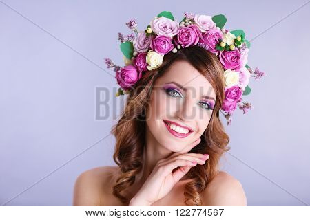 Beautiful young woman wearing floral headband on a grey background