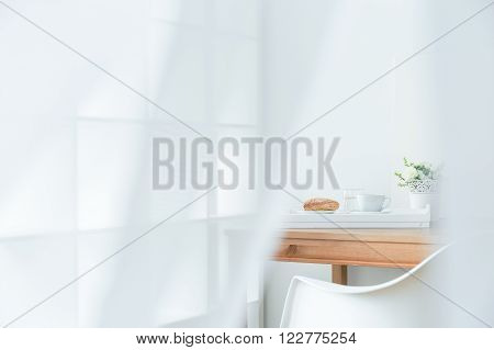 Close up of white interior with modern chair and wood table, salver with breakfast standing on table