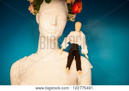 small figure man on the shoulder of the dummy in a wreath.