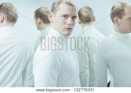 Duplicated image of man with mental problem standing in white interior.