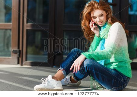 Young beautiful woman with red curly long hair and green eyes,light makeup and pink nail Polish,dressed in a knitted sweater white-green color,the neck is blue-green light scarf,talking on a cell phone in the city autumn