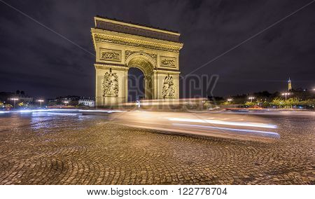 Night time in Arc de Triomphe and blurred cars traffic along the traffic circle